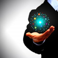 Businessman holding a globe with information technology icons in his palms - Information Technology concept
